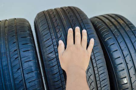 traction: Close up of person checking examining car tyre on the shelf abstract transportation background. Automobile warehouse business, factory production. Protector surface texture Stock Photo