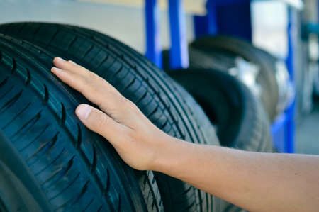 Close up of person checking examining car tyre on the shelf abstract transportation background. Automobile warehouse business, factory production. Protector surface texture Stock Photo