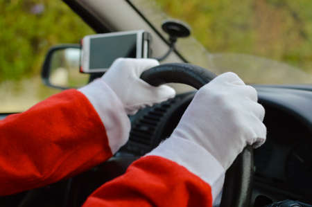 Santa Claus driving car and using mobile smartphone abstract natural outdoors background. Closeup on person hands holding wheel. Festive busy joyful time, modern communication delivery GPS technology. Standard-Bild