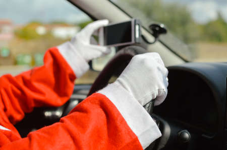 Santa Claus driving car and using mobile smartphone abstract natural outdoors background. Closeup on person hands holding wheel. Festive busy joyful time, modern communication delivery GPS technology. Stock Photo
