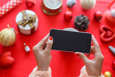 Top side view of hands using mobile phone on red background with Christmas gifts. Xmas Happy New Year composition. Flat lay display design for text message, watching video, game play, wish list