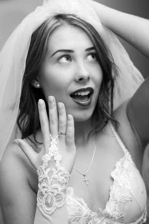 Black and white closeup of beautiful sensual young lady showing engagement ring and happy smiling looking up