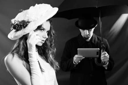 Black and white photography of beautiful young lady wearing hat and talking on mobile phone over male with tablet pc computer and umbrella