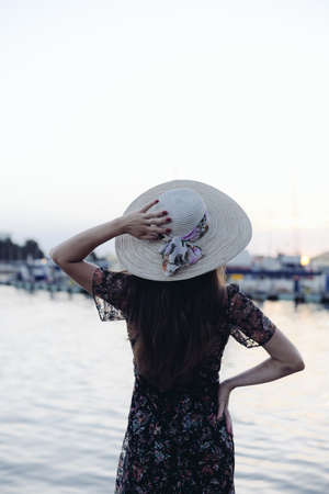 Back side view of attractive woman having fun enjoying summer holiday weekend background. Harbor outdoors, amazing dreamy marine vacation freedom pleasure concept
