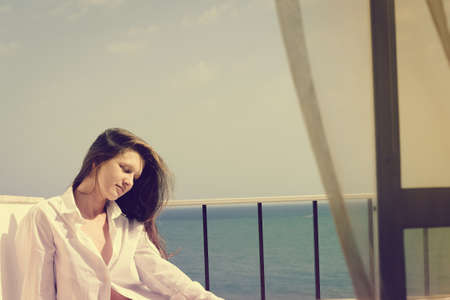 Back side view of cheerful beautiful woman enjoying healthy relax lifestyle looking out window having positive day and bright sunny oceanfront outdoors background. Travel relaxation destination Stock Photo