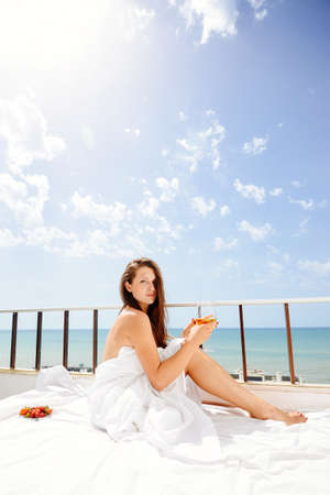Cheerful beautiful woman enjoying healthy relax lifestyle drinking hot beverage looking out window having positive day and bright sunny oceanfront outdoors background. Travel relaxation destination