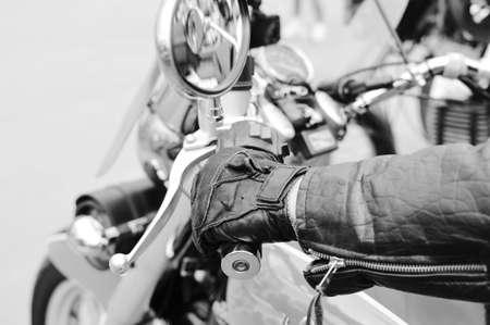 Black and white photography of hand on motorbike handlebar. closeup