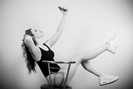 Black and white picture of gorgeous sexy fitness girl with perfectly fit body making selfy on chair Stock Photo