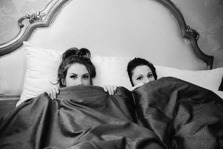 Black and white picture of scared friends girls watching horror movie on tv at home laying in bed