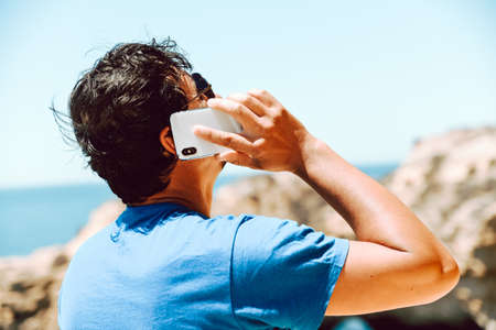 Man holding mobile phone nature blue sky outdoors. Closeup on handsome person use wireless digital smartphone device, modern design, communication technology lifestyle
