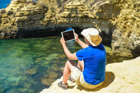 Back side view of person sitting holding tablet computer on ocean sunny natural background. Traveler having fun on international travelling lifestyle, technology social communication, amazing nature Stock Photo