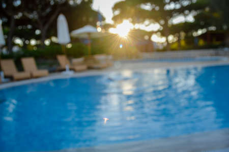 Defocused blurry recreational holiday swimming pool sunny tropical background. Unfocused blurred outdoors for having fun on travel vacation summertime relax lifestyle