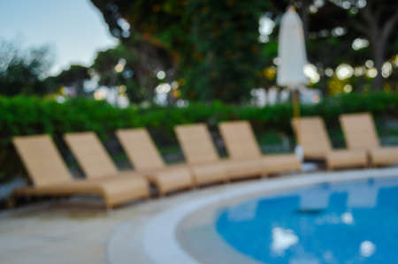 Defocused blurry recreational holiday swimming pool sunny tropical background. Unfocused blurred outdoors for having fun on travel vacation summertime relax lifestyle Stockfoto - 106347016