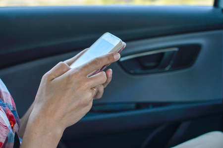 Closeup on person holding using mobile phone on the car interior background, modern smart computer apps solution and online network