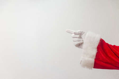 Santa Claus pointing finger show direction on a light texture background. Seasonal closeup of holiday excitement and hope