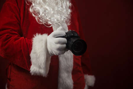 Santa Claus using holding in hands DSLR camera. Christmas and New Year celebration background