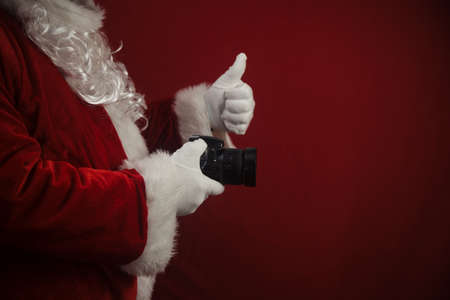 Santa Claus using DSLR camera taking images showing thumb up. Happy Christmas Evening and New Year celebration background. Fun loving creative costume time Stockfoto