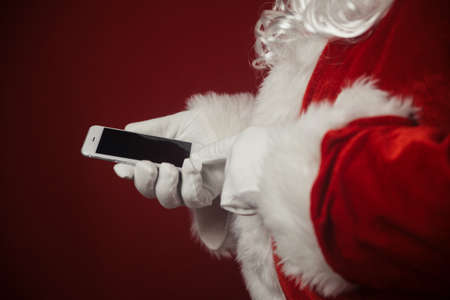 Santa Claus using working on mobile phone. Closeup image of modern communication technology. Telephone call, sending text message, taking photography and filming video during joyful happy time Stockfoto - 116005045