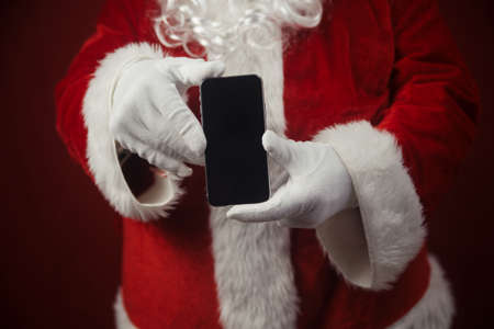 Santa Claus using working on mobile phone. Closeup image of modern communication technology. Telephone call, sending text message, taking photography and filming video during joyful happy time Stockfoto - 116005059
