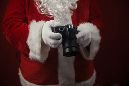 Santa Claus using holding in hands DSLR camera. Christmas and New Year celebration background Stockfoto - 116153538