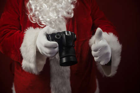 Santa Claus using DSLR camera taking images showing thumb up. Happy Christmas Evening and New Year celebration background. Fun loving creative costume time Stockfoto - 116153539