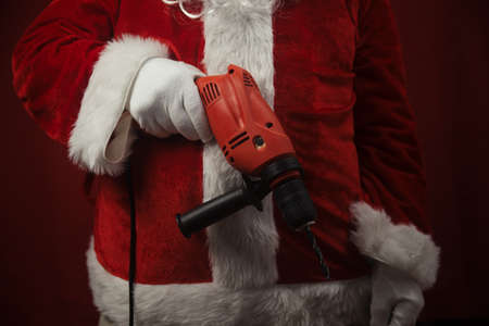 Santa Claus holding using electric drill tools ready to renovate space background. Handyman repairman in festive mood for seasonal business repairs work. Merry Christmas and Happy New Year!