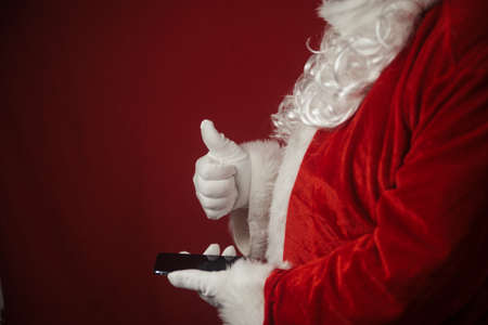 Santa Claus using working on mobile phone. Closeup image of modern communication technology. Telephone call, sending text message, taking photography and filming video during joyful happy time Stockfoto