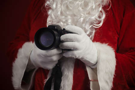 Santa Claus using holding in hands DSLR camera. Christmas and New Year celebration background Stockfoto - 116153555
