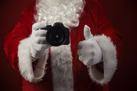 Santa Claus using DSLR camera taking images showing thumb up. Happy Christmas Evening and New Year celebration background. Fun loving creative costume time Stockfoto - 116153556
