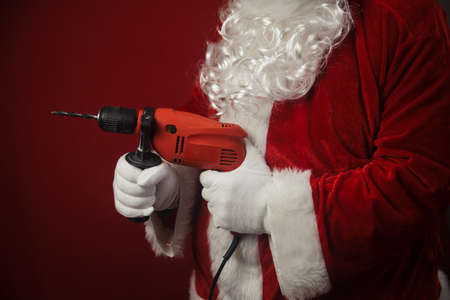 Santa Claus holding using electric drill tools ready to renovate space background. Handyman repairman in festive mood for seasonal business repairs work. Merry Cristmas and Happy New Year!