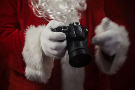 Santa Claus using DSLR camera taking images showing thumb up. Happy Christmas Evening and New Year celebration background. Fun loving creative costume time Stock fotó