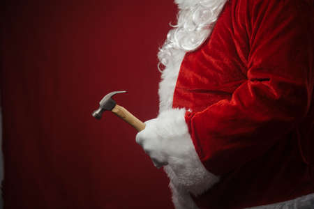 Santa Claus holding hammer in hands busy preparing decoration. Closeup view of creative ideas design, taking job assignments renovation time. Happy Christmas and New Year background Stock Photo