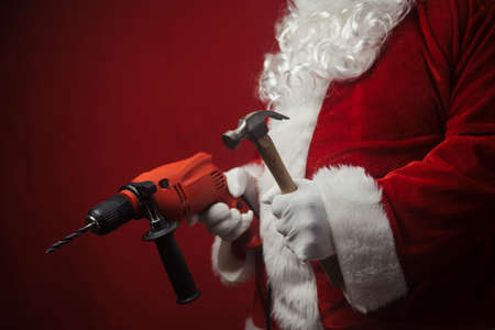Father Santa Claus holding using electric drill and hammer tools ready to renovate space background. Handyman repairman in festive mood for seasonal business work. Merry Christmas and Happy New Year! Stockfoto - 116153565