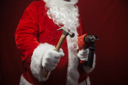 Santa Claus holding hammer and drill in hands busy preparing decoration. Closeup view of building creative ideas, taking job. Happy Christmas and New Year time renovation design background Stock Photo