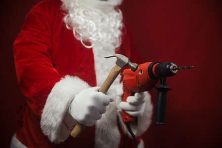 Santa Claus holding hammer and drill in hands busy preparing decoration. Closeup view of building creative ideas, taking job. Happy Christmas and New Year time renovation design background Stockfoto