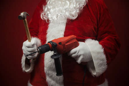 Father Santa Claus holding using electric drill and hammer tools ready to renovate space background. Handyman repairman in festive mood for seasonal business work. Merry Christmas and Happy New Year!