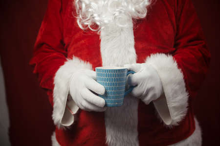 Relaxing Santa Claus drinking holding hot mug, festive leisure lifestyle closeup image. Merry Christmas and Happy New Year amazing excitement joyful seasonal holidays time!