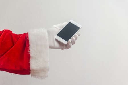 Santa Claus using mobile phone modern smartphone communication technology background. Closeup mock up view. Business service solution and traditional holidays Stock Photo