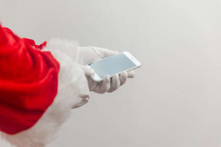 Santa Claus using mobile phone modern smartphone communication technology background. Closeup mock up view. Business service solution and traditional holidays Stockfoto