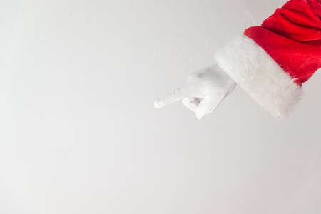 Santa Claus pointing finger. Direct approval guide trend. Closeup view of father xmas gloved hand in red costume show gesturing on white space background Stockfoto