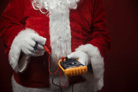 Closeup on Santa Claus solving electricity problems using holding digital tester multimeter electronic measure equipment. Ready for Merry Christmas and Happy New Year celebration background