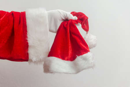Santa Claus holding in hands red hat on white seasonal background. Ready for festive time. Merry Christmas and Happy New Year close up photography Stockfoto
