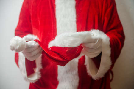 Santa Claus holding in hands red hat on white seasonal background. Ready for festive time. Merry Christmas and Happy New Year close up photography Stock Photo