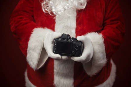 Santa Claus using holding in hands DSLR camera showing screen display. Closeup of creative ideas work, taking shooting images. Happy Christmas and New Year celebration design background Stockfoto