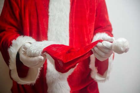 Santa Claus holding in hands red hat on white seasonal background. Ready for festive time. Merry Christmas and Happy New Year close up photography Stockfoto - 116005355