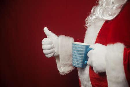 Relaxing Santa Claus drinking holding hot mug, festive leisure lifestyle closeup image. Merry Christmas and Happy New Year amazing excitement joyful seasonal holidays time!