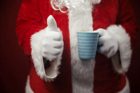Relaxing Santa Claus drinking holding hot mug, festive leisure lifestyle closeup image. Merry Christmas and Happy New Year amazing excitement joyful seasonal holidays time! Stockfoto - 116005359
