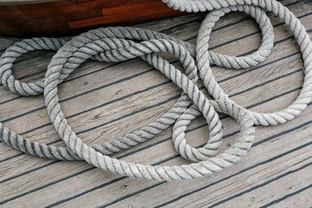 coiled rope: Overhead view of neatly coiled rope on a wooden deck