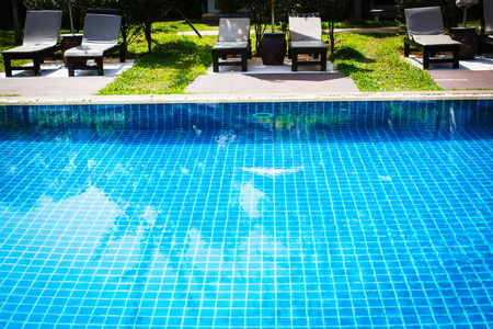 Swimming pool with reflection of trees in it