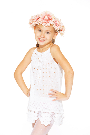 only teenage girls: Little girl posing for the camera in white dress with wreath